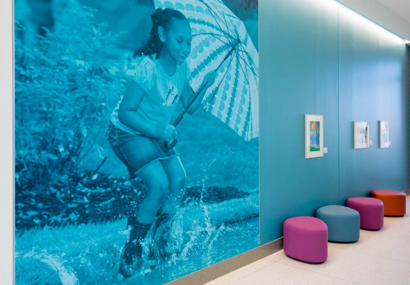 "As part of the overarching ""Backyard"" theme of Kay Jewelers Pavilion, our ER's puddle theme features a calming blue palette, splashes of artwork, ripple patterns in the flooring and an aquarium."